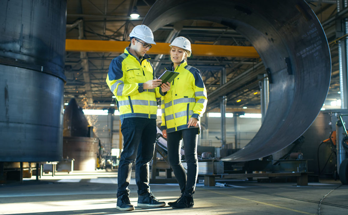 Male and Female Industrial Engineers in Hard Hats Discuss New Pr